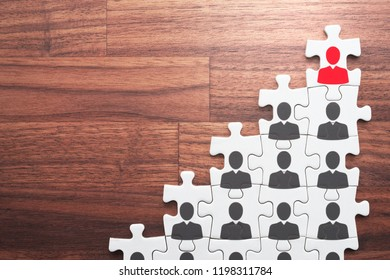 Career development and promotion concept. Going and standing on height. Personal growth and development. Assembling jigsaw puzzle pieces on wood desk.