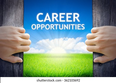 Career Opportunities. Hand opening an old wooden door and found Career Opportunities word floating over green field and bright blue Sky Sunrise.