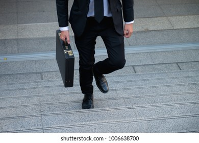 Career path or business growth concept : Lower part of businessman in formal suit walking up the outdoor stair.