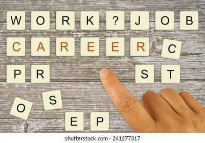 Career planning, recruitment etc. Finger pointing making choice with letter tiles.