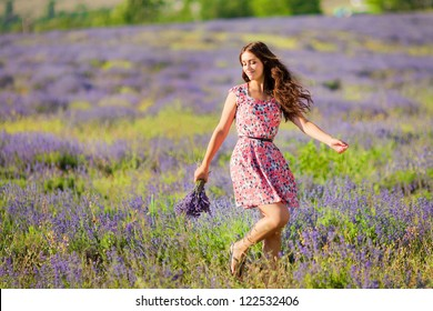 Carefree adorable girl with bouquet in fairy field of lavender. Summer freedom enjoy concept