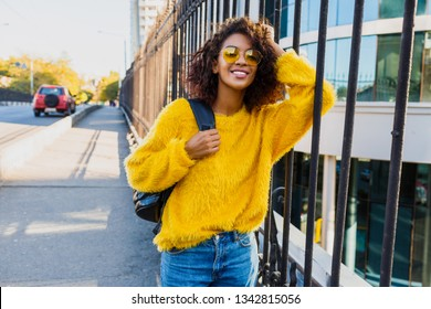 Carefree African woman walking in New York City across the bridge with back. Traveling student. Positive mood.
