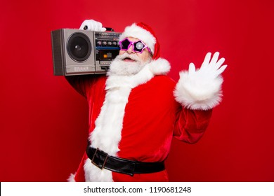Carefree aged mature stylish Santa with white beard in costume star spectacles gloves listen the best retro audio sound on vintage record isolated winter december noel eve red background