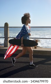 Carefree american woman walking with longboard and USA flag around her shoulders, summer holiday