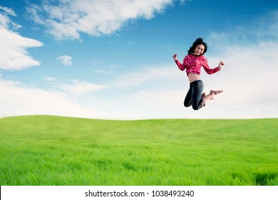 Carefree Asian woman making a big jump on meadow. Summer or Spring concept
