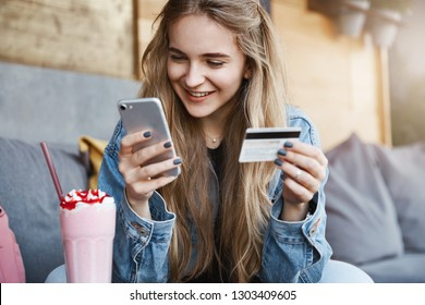 Carefree attractive fair-haired female friend in trendy denim jacket, holding credit card and smartphone, gazing at screen with smile while sending money to girlfriend who paid for drinks