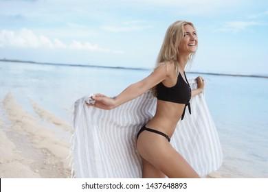 Carefree attractive happy blond woman dancing wearing bikini hold beach towel look up ski enjoy warm sun sunbathing summer vacation stand ocean shore tropical island holidays together boyfriend