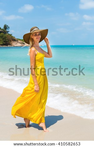 Carefree beautiful fashion blonde woman in beach straw hat walking barefoot  by sand of tropical beach and holding her long yellow dress. Natural woman  ... f35dd27b8038