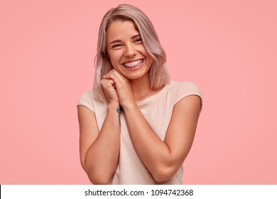 Carefree beautiful female with braces on teeth, smiles broadly at camera, being in high spirit while hangs out with friends, has joyful expression, stands against pink background. Optimistic girl