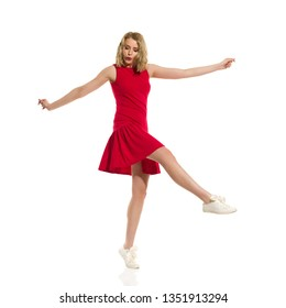 Carefree beautiful young woman in red mini dress and sneakers is standing on one leg, dancing, looking away and whistle. Full length studio shot isolated on white.