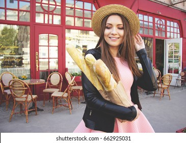 Carefree beauty. Portrait of cheerful and beautiful young woman in hat and pink dress keeping baguettes in her hands and touching hair while standing against French cafe.