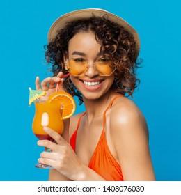 Carefree black girl enjoying fruit non-alcoholic cocktail, blue studio background. Summer time concept