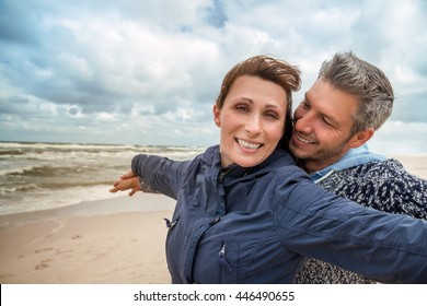 carefree boyfriend with girlfriend on windy coast