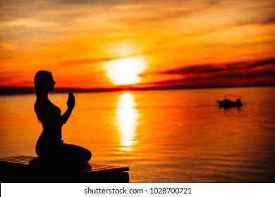 Carefree calm woman meditating in nature.Finding inner peace.Yoga practice.Spiritual healing lifestyle.Enjoying peace,anti-stress therapy,mindfulness meditation.Positive energy.Chakra balancing