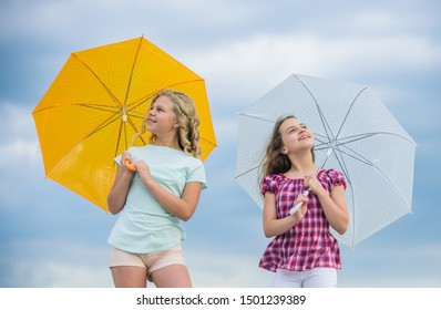 Carefree children outdoors. Girls friends with umbrellas cloudy sky background. Freedom and freshness. Weather forecast. Ready for any weather. Windy or rainy we are prepared. Weather changing.