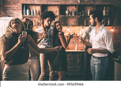 Carefree dance with friends. Cheerful young people dancing and drinking while enjoying home party on the kitchen