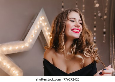 Carefree fashionable woman playing with shiny curly hair on dark background. Relaxed young lady with romantic hairstyle laughing in studio during holiday photoshoot.