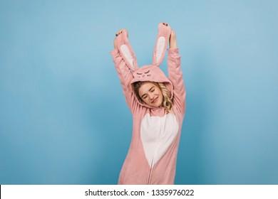 Carefree female model dancing in pink kigurumi. Studio shot of emotional girl wears bunny costume.