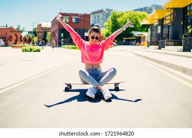 Carefree female skater 20s enjoying freedom youth lifestyle sitting at girlish skateboard and raising hands in air, happy woman dressed in trendy streetwear spending day for active board hobby