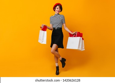 Carefree french lady posing after shopping. Adorable woman in red beret holding store bags.