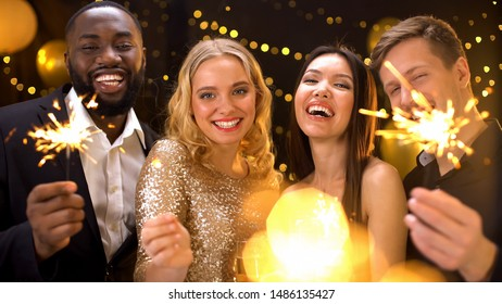 Carefree friends enjoying new year celebration in night club, holding sparklers