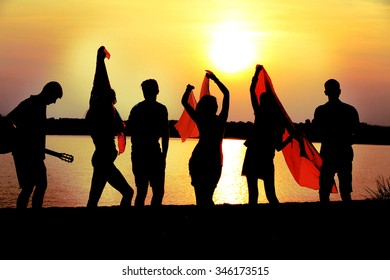 Carefree friends have fun on sunset near water