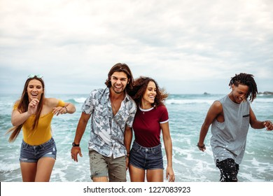 Carefree friends having fun along the sea shore. Young people walking and enjoying a day on beach vacation.
