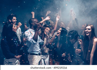 Carefree fun. Group of beautiful young people throwing colorful confetti and looking happy