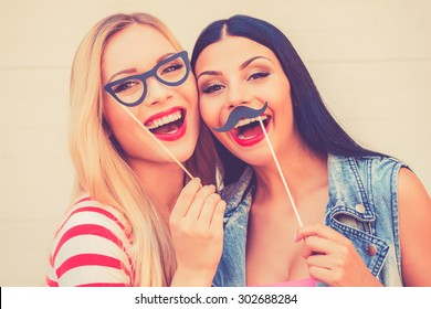 Carefree fun. Two cheerful young women making faces while standing outdoors