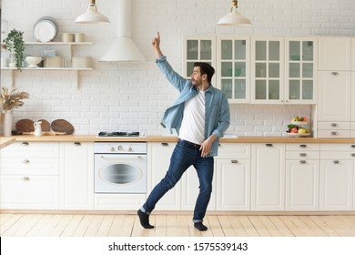 Carefree funny young man having fun dancing alone in modern kitchen interior, active happy funky single guy enjoying silly movements dance standing at home listening music celebrating freedom concept