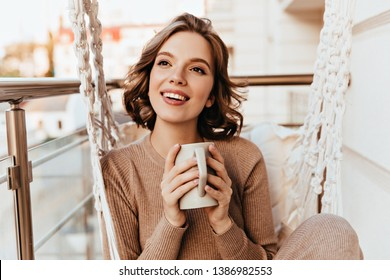 Carefree girl with brown makeup drinking tea at balcony. Photo of pleasant brunette woman in knitted dress enjoying coffee.