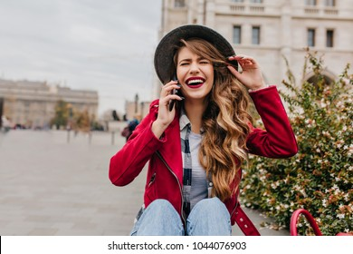 Carefree girl in elegant hair sitting on the ground and talking on phone. Outdoor portrait of blissful long-haired woman in red jacket laughing while calling someone.