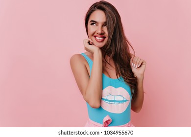Carefree girl with long hairstyle looking away with smile. Studio shot of dreamy brunette woman in blue attire isolated on pink background.