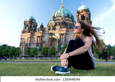 carefree girl relax in germany at berlin cathedral. pretty girl relax on summer grass near berlin cathedral in germany. just relaxing. moments of joy. no rush. girl tourist with long windy hair relax