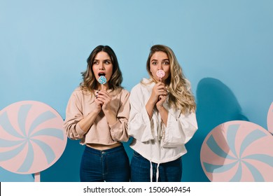 Carefree girls licking candies. Studio shot of trendy ladies with lollipops posing on blue background.