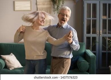 Carefree happy active old senior couple dancing jumping laughing in living room, cheerful retired elder husband holding hand of mature middle aged wife enjoy fun leisure retirement lifestyle at home