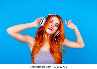 Carefree happy joyful girl with beautiful red curly long hair listen to music with white headphones  while standing on blue background