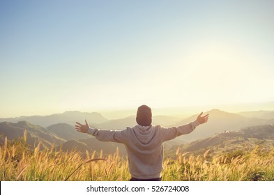 Carefree Happy Man Enjoying Nature on grass meadow on top of mountain cliff with sunrise. Beauty Outdoor. Freedom concept. Sunbeams. Enjoyment. copy space.
