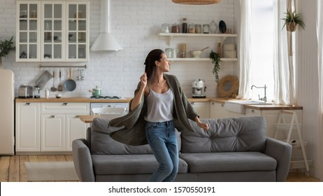 Carefree happy single young attractive woman dancing alone in modern kitchen interior, independent active lady having fun at clean home listening music enjoying freedom weekend time lifestyle at home