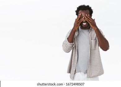 Carefree, happy smiling african-american bearded man in casual outfit, fool around, joking and laughing, cover eyes with hands, peek through fingers at camera, want see surprise, white background