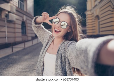 Carefree and happy, sunny spring mood. Cute young smiling girl is making selfie on a camera while walking outdoors. She is wearing casual outfit, mirror glasses