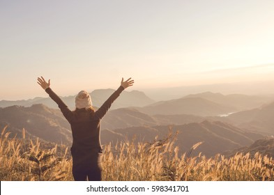Carefree Happy Woman Enjoying Nature on grass meadow on top of mountain cliff with sunrise. Beauty Girl Outdoor. Freedom concept. Len flare effect. Sunbeams. Enjoyment. copy space.