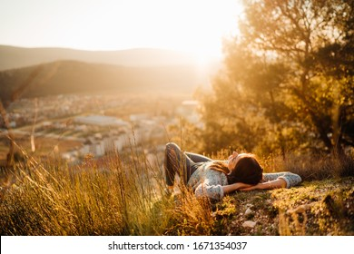 Carefree happy woman lying on green grass meadow on top of mountain enjoying sun on her face.Enjoying nature sunset.Freedom.Relaxing in mountains at sunrise.Sunshine.Daydreaming.Listening to music