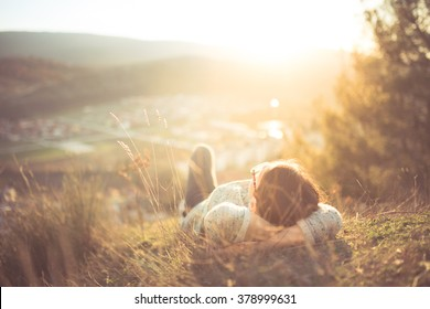 Carefree happy woman lying on green grass meadow on top of mountain edge cliff enjoying sun on her face.Enjoying nature sunset.Freedom.Enjoyment.Relaxing in mountains at sunrise.Sunshine.Daydreaming - Shutterstock ID 378999631