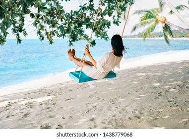 Carefree happy woman on swing on beautiful paradises beach. Relax and freedom concept