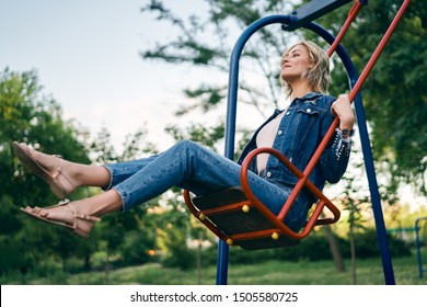 Carefree happy woman on swing outdoors. Happiness and fun concept