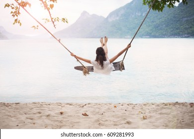 Carefree happy woman on swing on beautiful paradises beach in Thailand