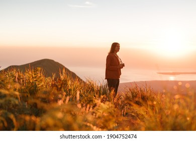 Carefree happy woman in sweater enjoying nature on grass meadow on top of mountain with sunrise. Beauty girl outdoor with sunbeams. Freedom concept