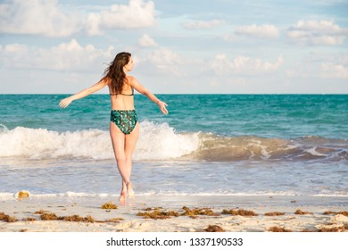 Carefree and happy young brunette woman on the beach in the Mayan Riviera, Mexico