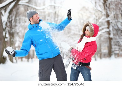 Carefree happy young couple having fun together in snow in winter woodland throwing snowballs at each other during a mock fight